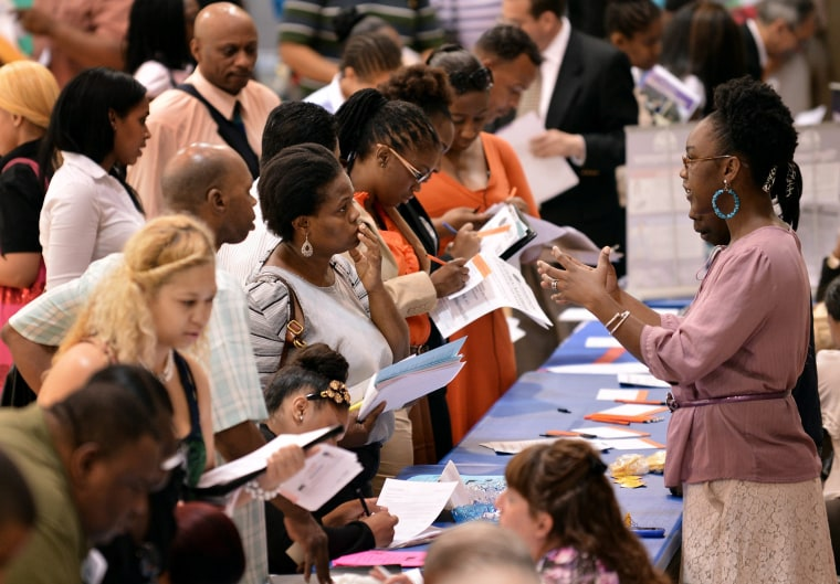 People talking with prospective employers during a job fair at a community center in New York, NY, August 15, 2012.