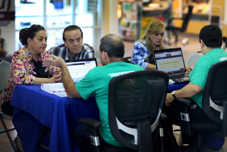 Marlene Gonzalez (L) and Alberto Gonzalez (2nd L) speak with Jose Luis Gonzalez (C), an insurance agent with Sunshine Life and Health Advisors, about purchasing insurance under the Affordable Care Act at a kiosk setup at the Mall of Americas on December 1