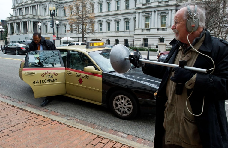 An activist dressed as spy using a listening device demonstrates at the Office of the U.S. Trade Representative in Washington, D.C., on December 16, 2013.