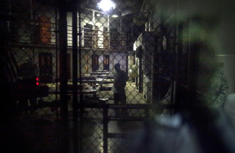 In this photo reviewed by the U.S. military, detainees behind a mirrored one-way window get ready for pre-dawn Islamic prayers in Camp VI detention facility at Guantanamo Bay Naval Base, Cuba, Nov. 20, 2013.