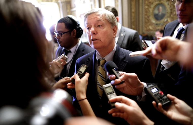 Sen. Lindsey Graham (R-SC) talks with reporters after stepping off the Senate floor at the U.S. Capitol Nov. 21, 2013 in Washington, DC.