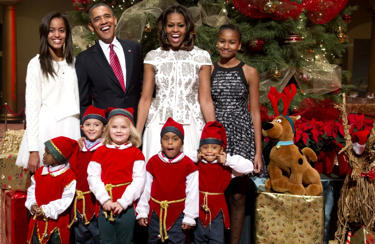US President Barack Obama, First Lady Michelle Obama and their daughters, Sasha (R) and Malia (L), pose for photographs alongside children dressed as elves in Washington on Dec. 15, 2013.