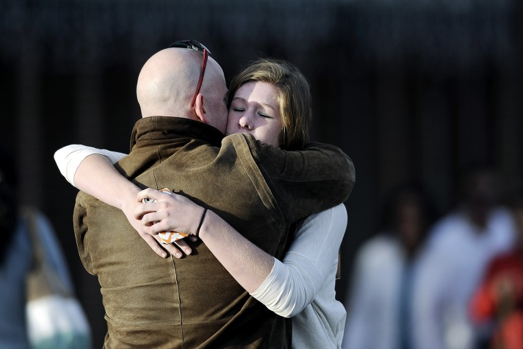 A man comforts a student outside Shepherd of the Hills Church after a school shooting at Arapahoe High School on Dec. 13, 2013 in Centennial, Colo.