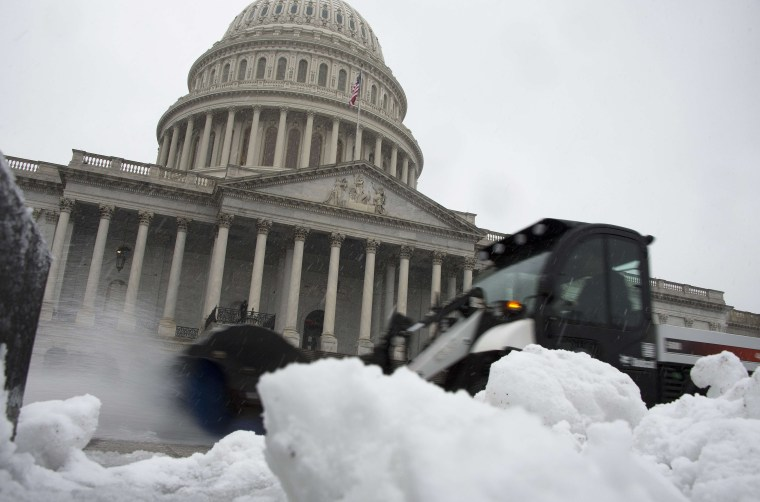 A snow plow passes by pushing away slush outside the U.S. Capitol Building in Washington, D.C., December 10, 2013.