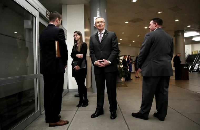 U.S. Senate Majority Leader Sen. Harry Reid (D-NV) (C) waits for the Senate subway after a vote December 17, 2013 on Capitol Hill in Washington, DC.