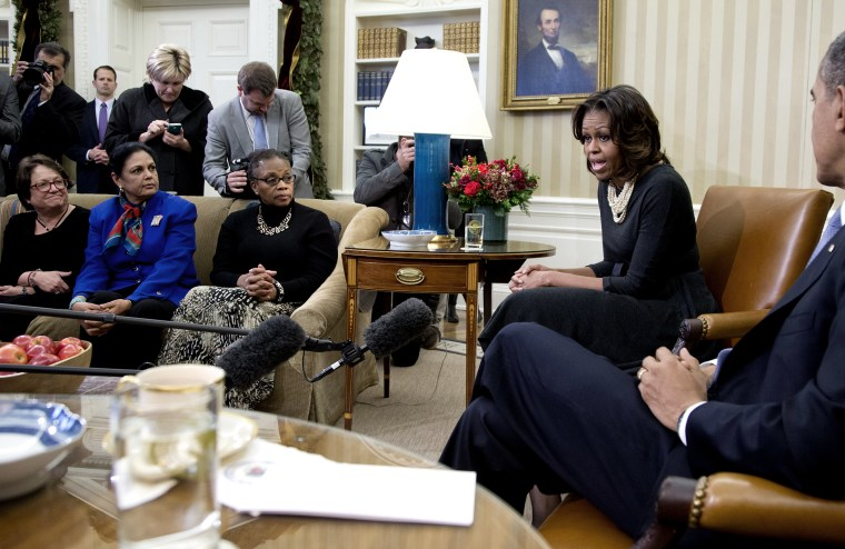 First Lady Michelle Obama speaks to the media as President Barack Obama listens as they meet with a group of mothers in the Oval Office of the White House in Washington, Dec. 18, 2013.