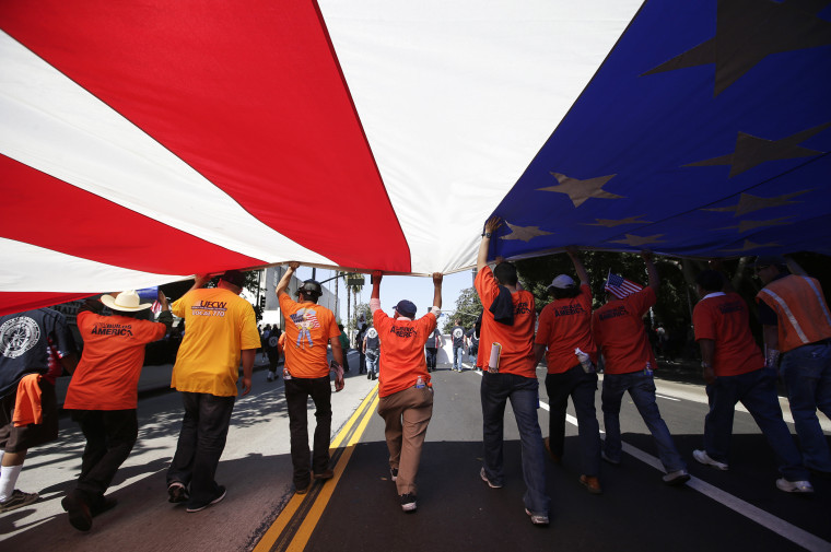 Union workers march along the street with a huge American flag during a May Day rally in Los Angeles, Calif., May 1, 2013.