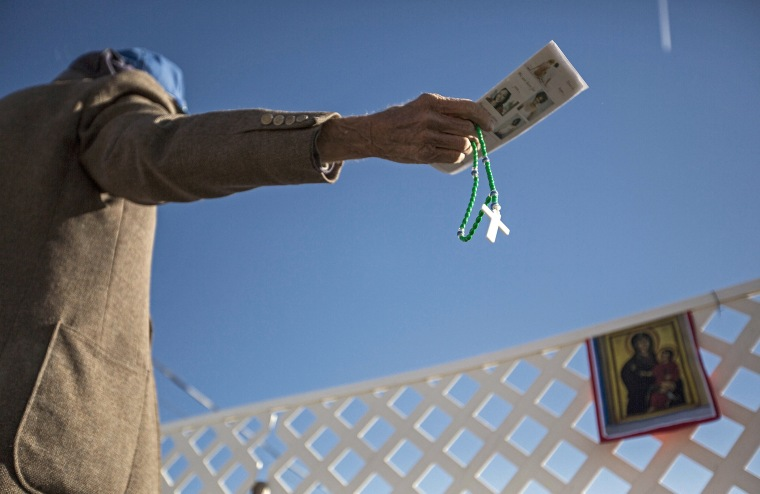A protester waves anti-abortion literature in the direction of a reproductive health clinic on Nov. 14, 2013, in Albuquerque, N.M.