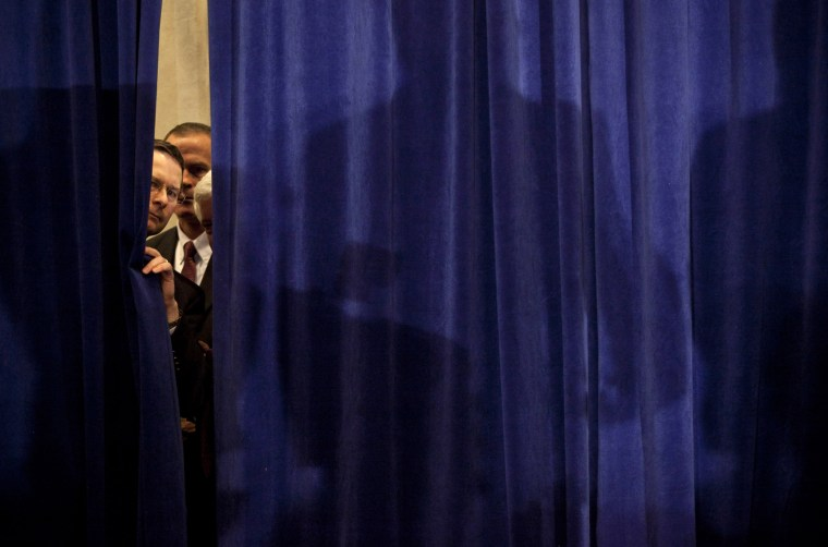 Security peeks through a curtain before Republican presidential candidate, former Speaker of the House Newt Gingrich arrived for a party on primary night January 10, 2012 in Manchester, New Hampshire.