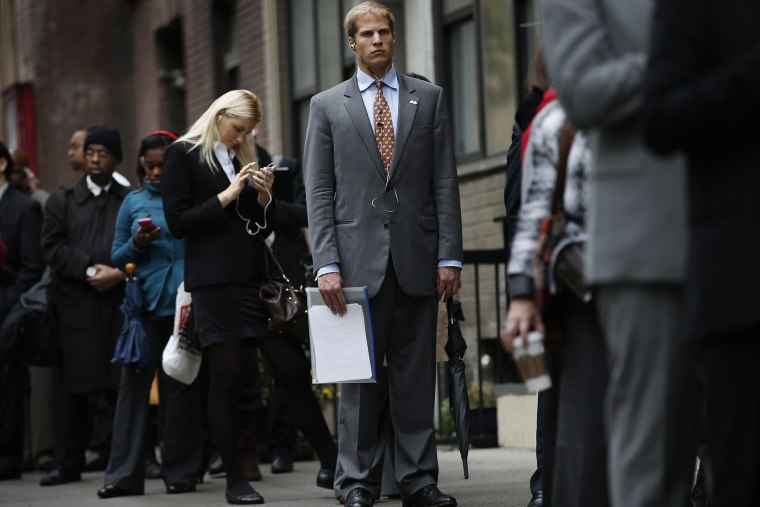 Job seekers stand in line to meet prospective employers at a career fair in New York City