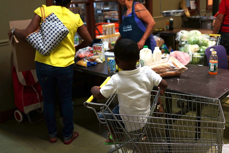 A child watches as his mother at the West Side Campaign Against Hunger food pantry as she shops for food on July 24, 2013 in New York, N.Y.