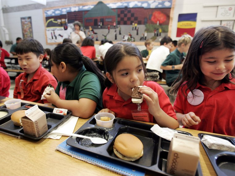 Elena Serrano, 7, second right, eats an ice cream sandwich during lunch at the Four Seasons Elementary School in St. Paul, Minn., June 29, 2006.