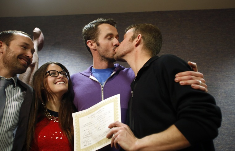The first gay couple to be married in Utah, Michael Ferguson (2nd R) and his husband Seth Anderson (R), kiss as Blake Ferguson (L) and his girlfriend Danielle Morgan watch after the pair married at the Salt Lake County Clerks office in Salt Lake City, Uta