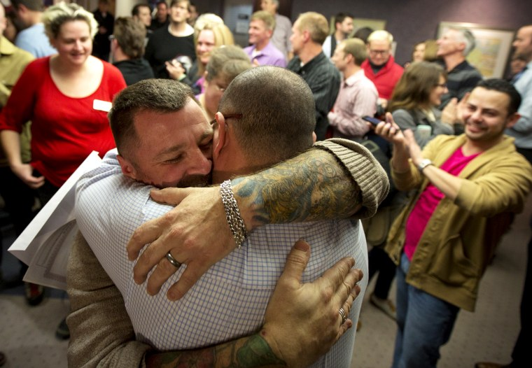 Chris Serrano, left, and Clifton Webb embrace after being married, as people wait in line to get licenses outside of the marriage division of the Salt Lake County Clerk's Office in Salt Lake City, Dec. 20, 2013.