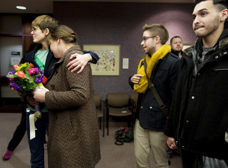Same-sex couples Natalie Dicou, left, and Nichole Christensen, middle left, and James Goodman, middle right, and Jeffrey Gomez, right, wait in line to get a marriage license at the Salt Lake County Clerk's Office in Salt Lake City, Dec. 20, 2013.