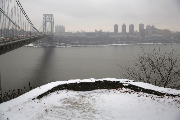 Snow covers the Palisades Interstate Park overlooking the George Washington Bridge between New York City (R), and Fort Lee, New Jersey on December 17, 2013.