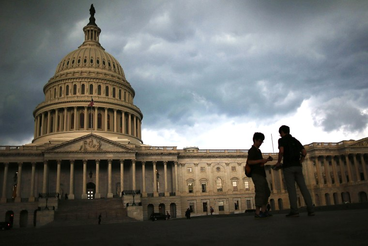 Two men stand on the plaza of the U.S. Capitol Building as storm clouds fill the sky, June 13, 2013 in Washington, DC.