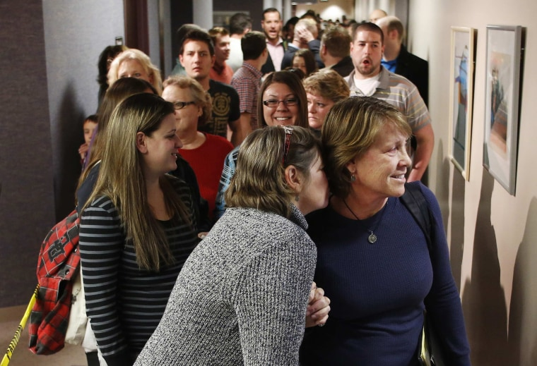 Same-sex couples, accompanied by their friends and family members, line up to get marriage licenses at the Salt Lake County Government Building in Salt Lake City, Utah, December 23, 2013.