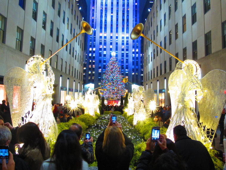 Tourists visit the Christmas tree at Rockefeller Center in New York City, December 5, 2013.
