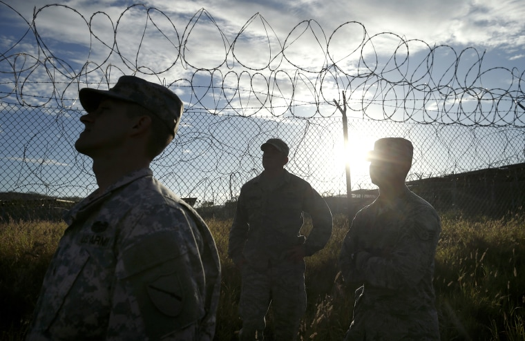 Military personnel walk in the now abandoned Camp X-Ray at Guantanamo Bay Naval Base, Cuba, Nov. 21, 2013.