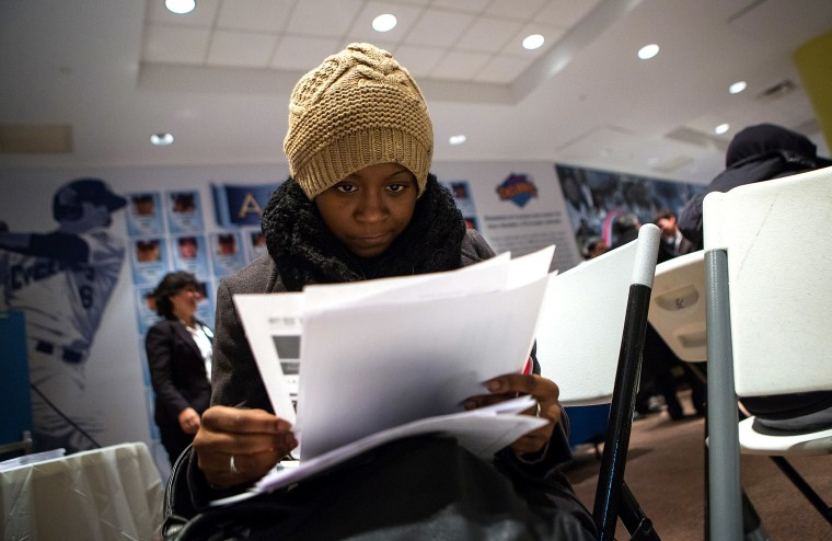 A woman fills out paperwork at a job training and resource fair at Coney Island in New York Dec. 11, 2013.