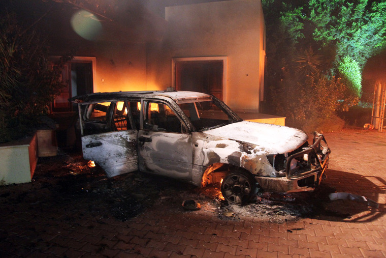 A vehicle and surrounding buildings smolder after they were set on fire inside the US mission compound in Benghazi., Sept. 11, 2012.