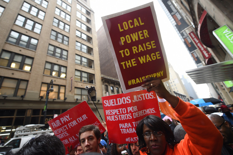 Fast-food workers hold placards in support to an increase of the fast food workers minimum wage in N.Y. on May 15, 2014. (Emmanuel Dunand/AFP/Getty)