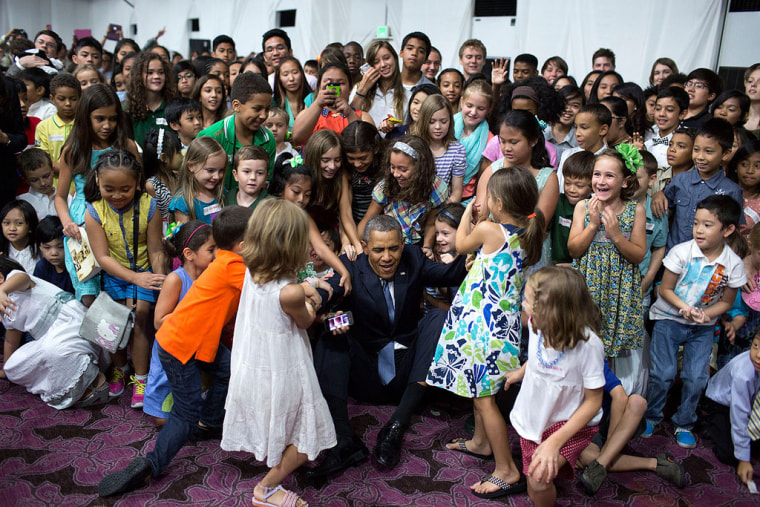 Children help President Barack Obama to his feet after he sat on the floor to have a group photo with them during a U.S. Embassy meet and greet at the Sofitel Philippine Plaza Manila in Manila, Philippines, April 28, 2014.