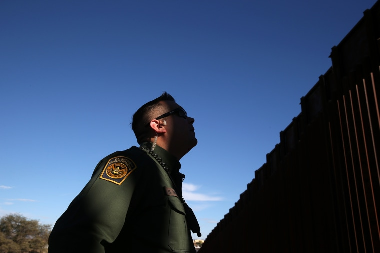 A U.S. Border Patrol agent stands next to the U.S.-Mexico border fence on Dec. 9, 2014 in Nogales, Ariz.