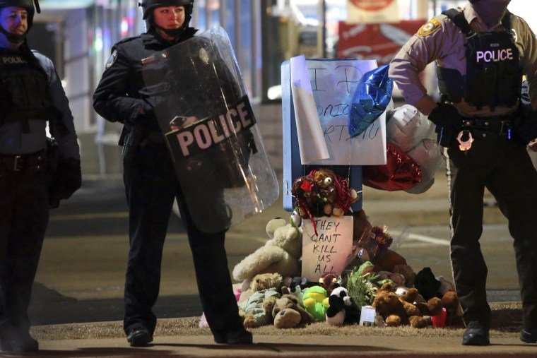 Police guard the entrance to a gas station in front of a memorial to Antonio Martin on Dec. 24, 2014, in Berkeley, Mo.