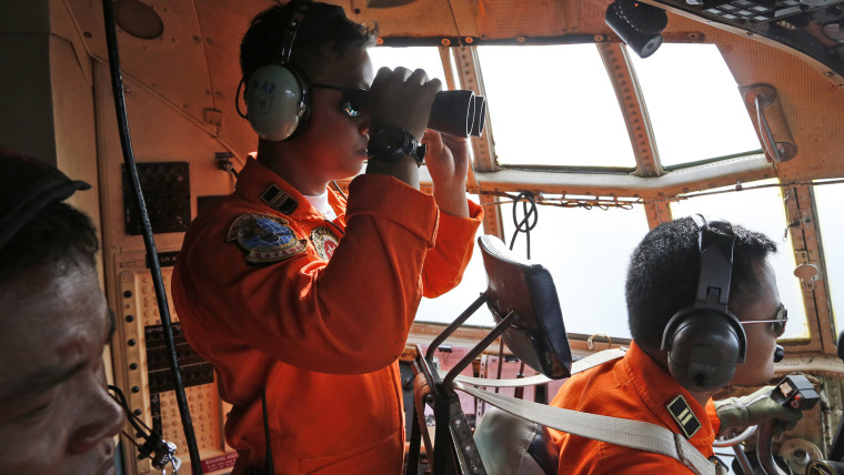 The crew of the Indonesian Air Force uses binoculars to scan the horizon during a search operation for the missing AirAsia flight 8501 jetliner on Dec. 29, 2014. (Dita Alangkara/AP)