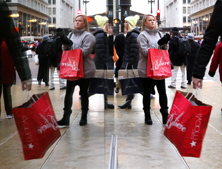 Last minute Christmas shoppers are reflected in a store's window as they walk through Chicago's Loop, Dec. 24, 2014. After enduring a brutal winter, businesses, consumers and investors showed renewed vigor as 2014 wore on and set themselves apart from much of the world.