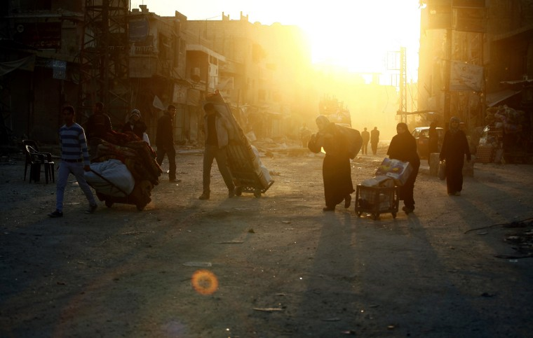 Syrian civilians carry their belongings they found at their homes destroyed during clashes between the Free Syrian Army and Syrian soldiers loyal to Syria's President Bashar Assad in the town of Hejeira, in the countryside of Damascus, Syria, Nov. 21, 201