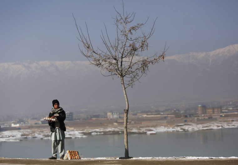 Zaryalai, 13, who sells boiled eggs, waits for customers during winter in Kabul January 1, 2014.