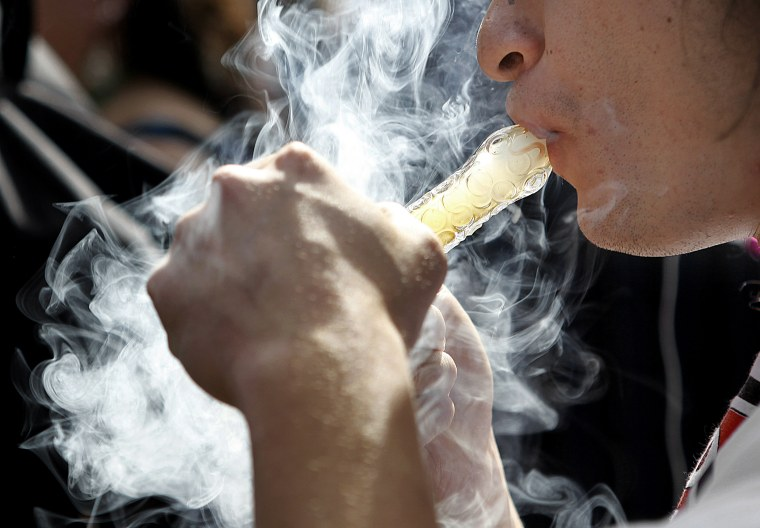 A man smokes as thousands gathered to celebrate the state's nedicinal marijuana laws and collectively light up at 4:20 p.m. in Civic Center Park April 20, 2012 in Denver, Colo.