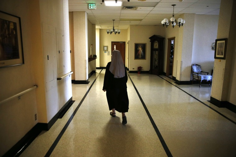 Mother Patricia Mary walks in the hallway at the Mullen Home for the Aged, run by Little Sisters of the Poor, in Denver, Colo., Thursday Jan. 2, 2014.