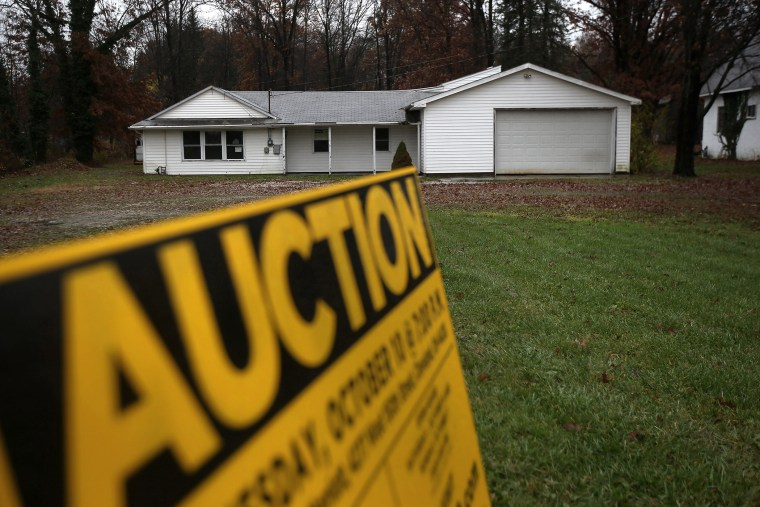 An auction sign stands in front of a foreclosed house on Oct. 29, 2012 in Warren, Ohio.