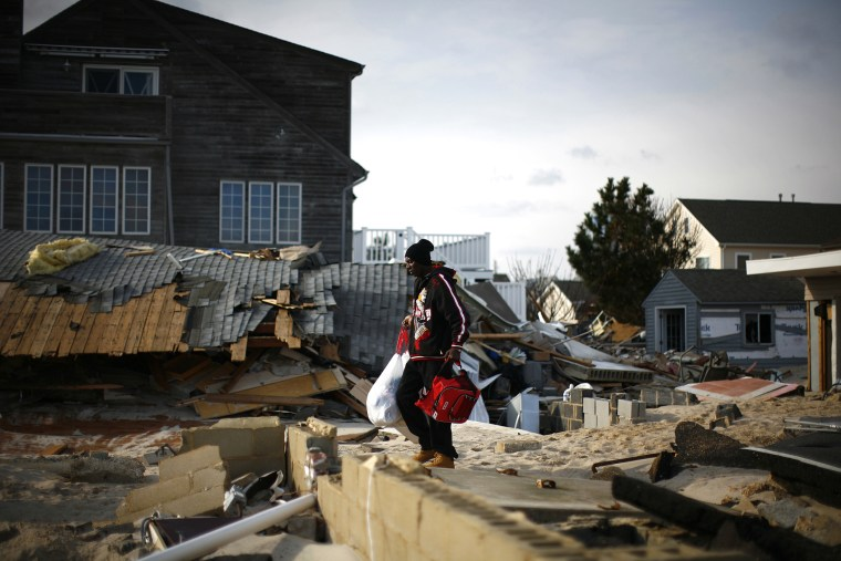 A man looks through homes damaged by Hurricane Sandy in Ortley Beach, New Jersey