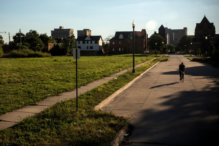 A man rides his bike past empty housing lots on September 5, 2013 in Detroit, Michigan.