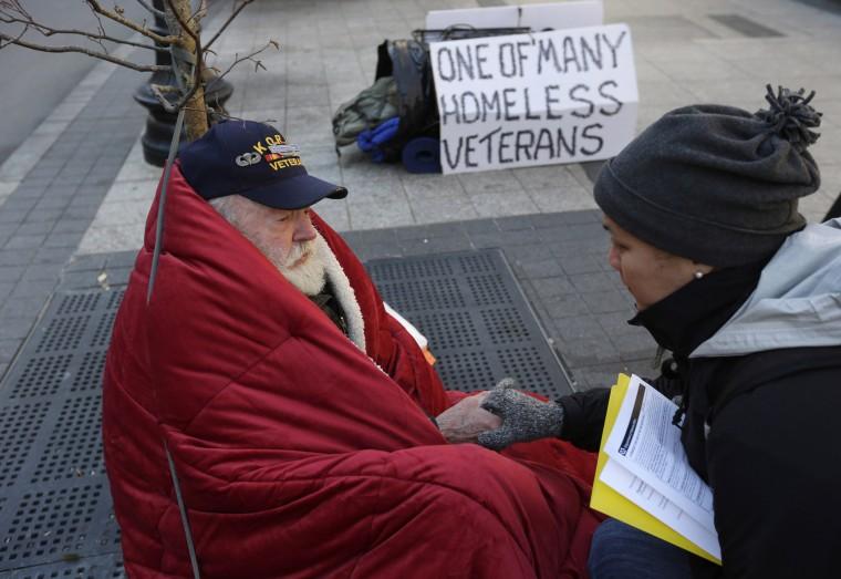 Homeless Korean War veteran Thomas Moore, 79, left, speaks with Boston Health Care for the Homeless street team outreach coordinator Romeena Lee on a sidewalk in Boston, Nov. 20, 2013.