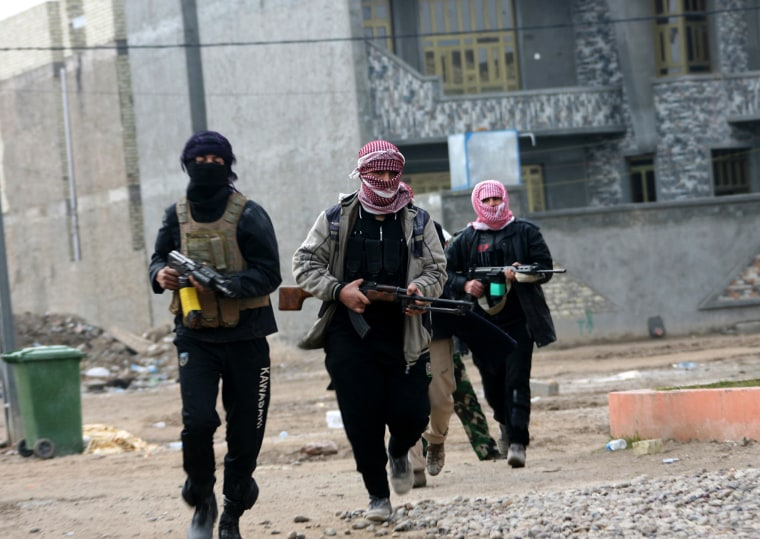 Gunmen patrol during clashes with Iraqi security forces in Fallujah, 40 miles west of Baghdad, Iraq, Jan. 5, 2014.