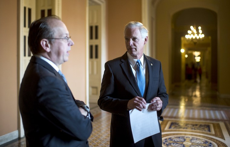 From left, Paul Clement, former United States Solicitor General, and Sen. Ron Johnson, R-Wisc., talk in the hallway before the start of their news conference on Jan. 6, 2014, to announce a lawsuit against the Office of Personnel Management challenging an