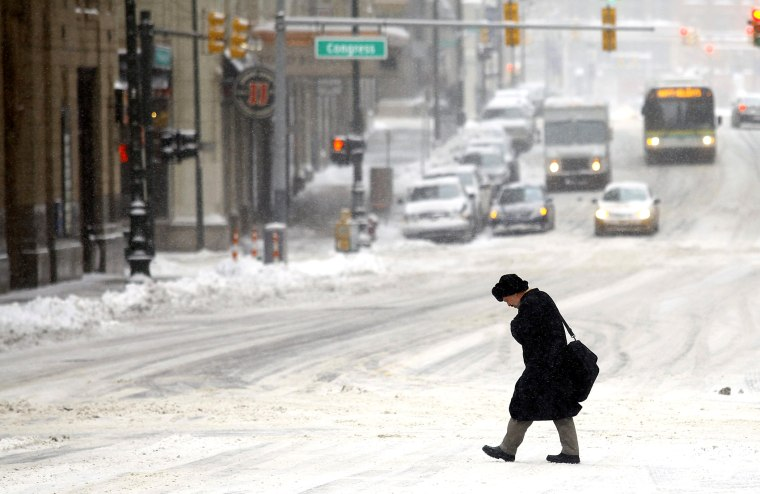 A man navigates through several inches of snow as the area deals with record breaking freezing weather Jan. 6, 2014 in Detroit, Mich.