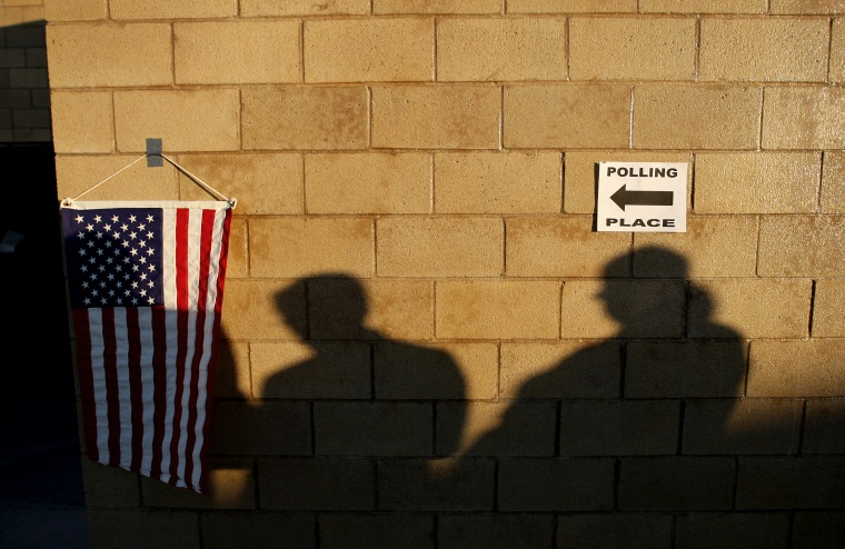 Voters cast shadows as they wait for their polling place in to open during the U.S. presidential election on Nov. 6, 2012 in the Los Angeles area community of Hermosa Beach, California.