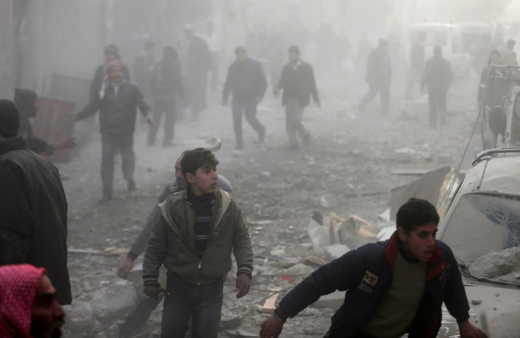 People rush after what activists said was an airstrike by forces loyal to Syrian President Bashar al-Assad in the Duma neighbourhood of Damascus