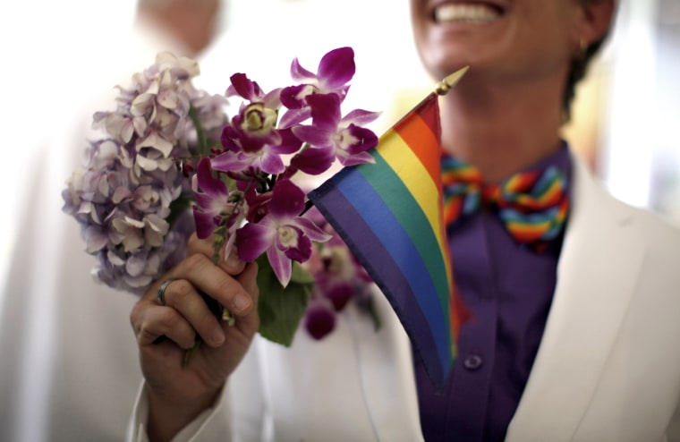 A woman holds a rainbow flag with her bouquet before getting married to her fiancee in West Hollywood, California, July 1, 2013.
