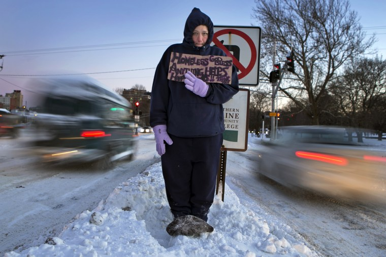 Victoria Morris, 28, panhandles in Portland, Maine, where the temperature at dusk was 7 degrees Fahrenheit, Jan. 3, 2014.