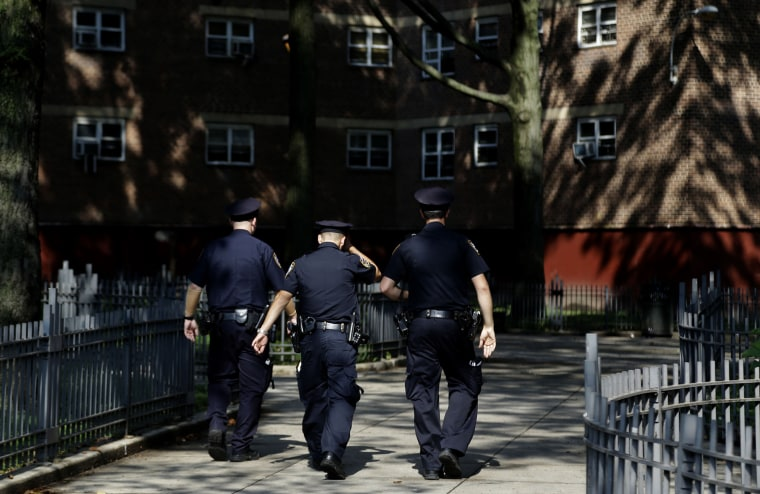 Police officers walk through the Brownsville Houses the Brownsville section of Brooklyn, New York, Tuesday, Aug. 13, 2013.