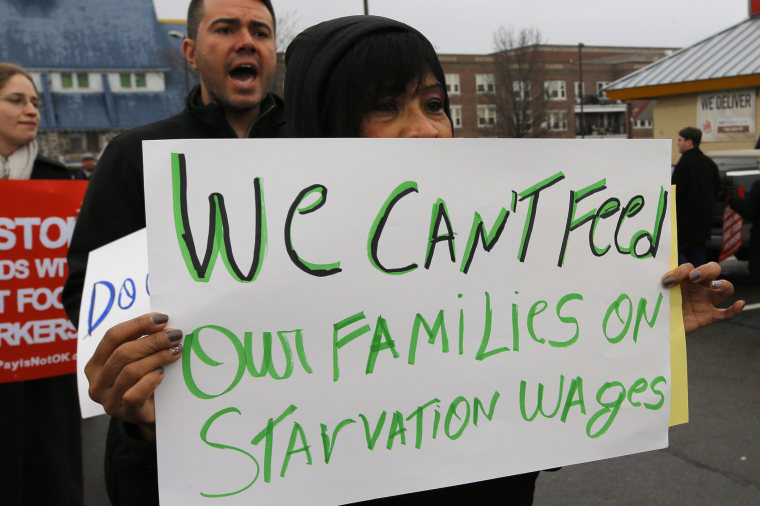 Gladys Jimenez holds a sign during a demonstration in support of higher minimum wages for fast food and other workers outside a Burger King restaurant in Boston, Massachusetts December 5, 2013.