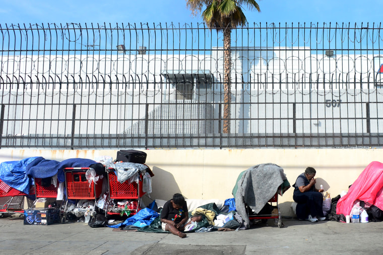Homeless women sit amid their belongings on a street in downtown Los Angeles, California, on January 8, 2014.